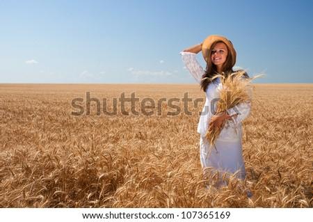 Happy girl in white dress on wheat field - stock photo