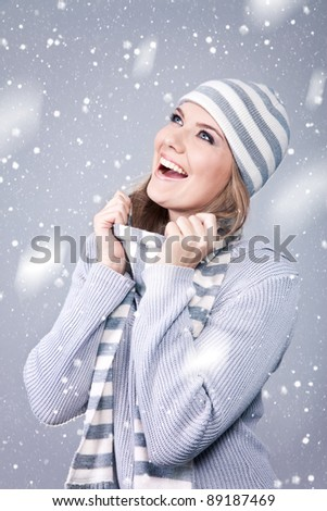 happy girl in  winter clothes, excitedly looking how its snowing - stock photo