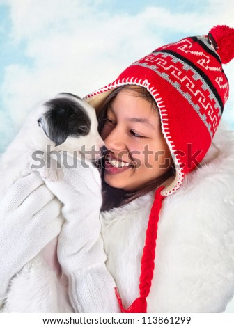 Happy girl in winter coat holding a 5 weeks old border collie puppy - stock photo
