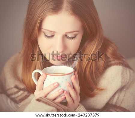 happy girl  is basking  under a blanket and a cup of coffee on a winter morning at home - stock photo