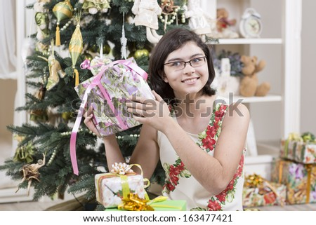 Happy girl is checking Christmas gifts