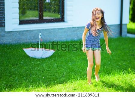 Happy girl is playing under rain on backyard - stock photo