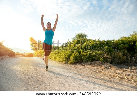 Happy girl jogging outdoors at sunset hour - stock photo