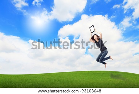 Happy Girl Jump and show touch pad computer on the meadow with blue sky and white cloud, , for cloud computing concept - stock photo