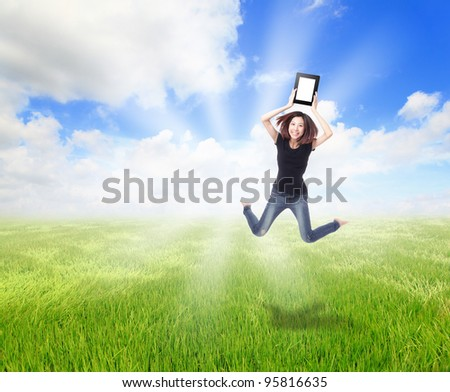 Happy Girl Jump and show touch pad computer on the meadow with blue sky and white cloud, for cloud computing concept - stock photo