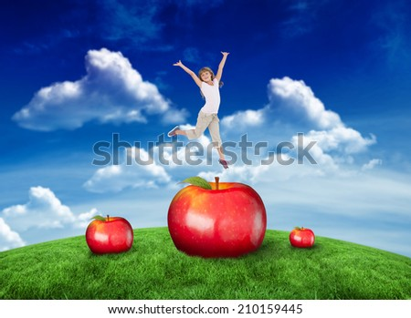 Happy girl jumping against green field under blue sky - stock photo