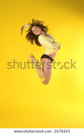 Happy girl jumping high on yellow - stock photo
