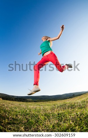 Happy girl jumping in nature, image shot with fish-eye lens