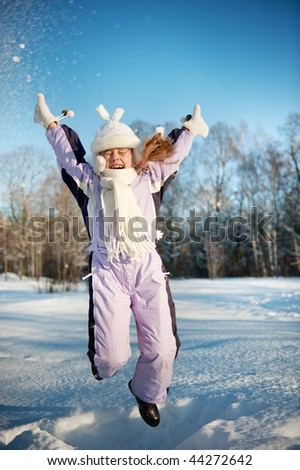 Happy girl jumping in the snow - stock photo