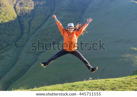 Happy girl jumping on green mountain hill - stock photo