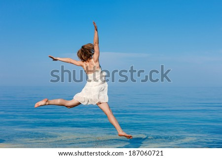 Happy girl jumping on the beach - stock photo