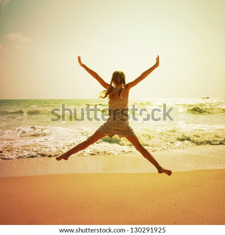 Happy girl jumping on the beach on the dawn time - stock photo