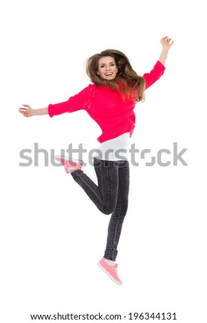 Happy girl jumping. Smiling young woman jumping with arms outstretched. Full length studio shot isolated on white. - stock photo