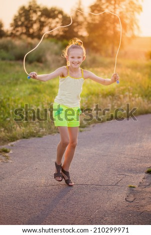 happy girl jumping with skipping rope outdoor - stock photo