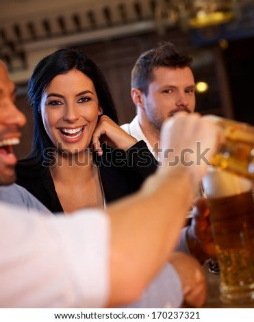 Happy girl laughing in pub, looking at camera, Friend pouring beer in the foreground. - stock photo