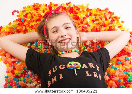 Happy girl laying in a pile of colorful candy including gummi bears, jelly beans, gumdrops and more.