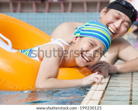 happy girl learning to swim in the swimming pool with father - stock photo
