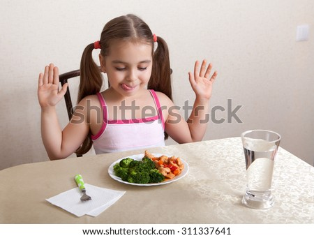 Happy girl licks lips, looking at the dish with meat and broccoli - stock photo