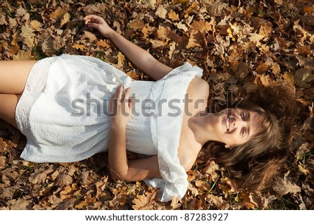Happy girl lies in oak leaves at autumn park