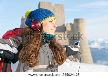 Happy girl listening to music on top of the mountain, Italy - stock photo