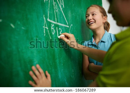 Happy girl looking at the blackboard at geometry lesson with her classmate near by - stock photo