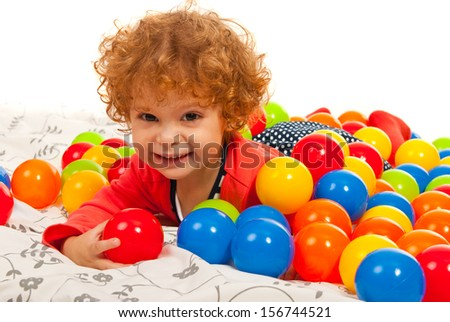 Happy girl lying down in the middle of many colorful balls  - stock photo