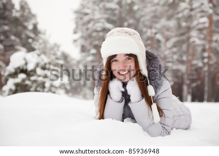 Happy girl lying down on the snow in winter - stock photo