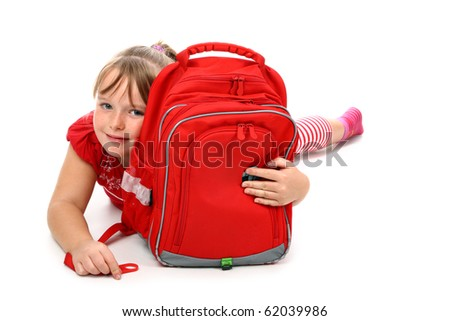 Happy girl lying on floor hugging red school bag smiling isolated on white
