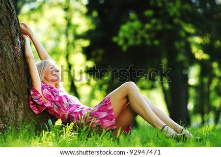 happy girl lying under a tree on a summer day - stock photo