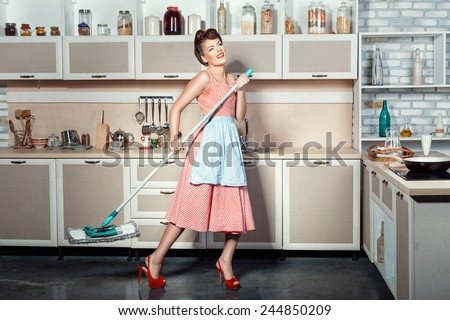 Happy girl makes cleaning the kitchen, hands holding a mop while singing. - stock photo