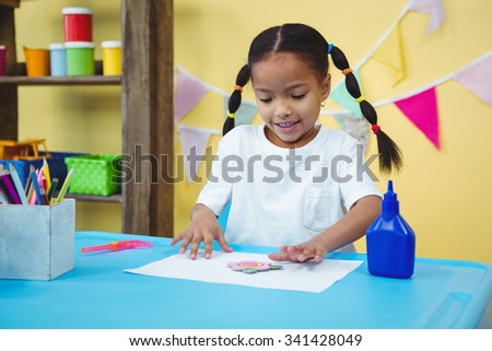 Happy girl making arts and crafts at her desk - stock photo