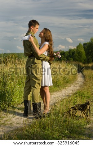 Happy girl meets a soldier. Return of the Soviet soldier in uniform of World War II home - stock photo
