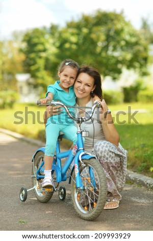 Happy girl on a bicycle with her mother in summer - stock photo