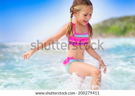 happy girl on a  tropical beach ocean has a fun with splash - stock photo