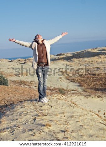 Happy girl on beach spring holiday in cheerful bliss enjoying the sunshine with arms outstretched  - stock photo