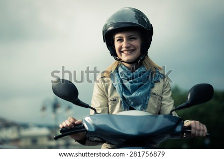 Happy girl on her scooter - stock photo
