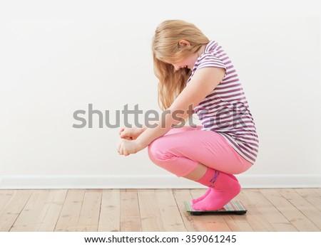 happy girl  on scales indoor - stock photo