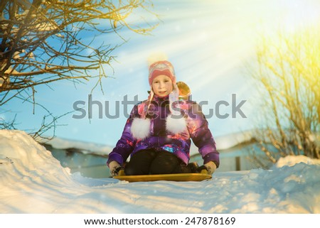 Happy girl on sled in winter outdoors. - stock photo
