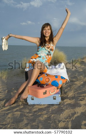 happy girl on the beach with colorful suitcases