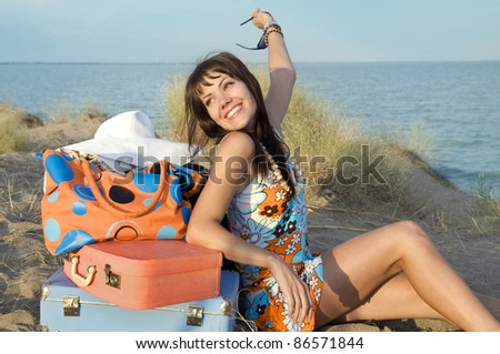 happy girl on the beach with colorful suitcases - stock photo