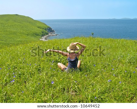 happy girl on the meadow against the sea landscape - stock photo