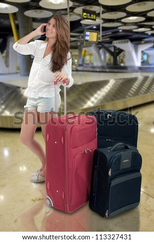 Happy Girl on the phone at the baggage claim at the airport - stock photo