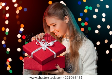 Happy girl opening in excitement Christmas box which is glowing inside. Excited woman. Christmas Gift - stock photo
