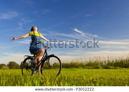 Happy girl over a bicycle and looking the view, in a green meadow - stock photo