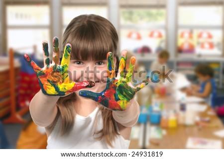 Happy Girl Painting With Her Hands in Kindergarten Class - stock photo