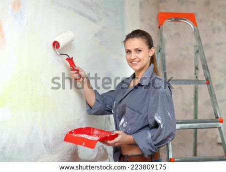 Happy girl paints wall with roller - stock photo