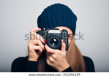 happy girl photographed in vintage camera, winter concept, studio photo isolated on a gray background - stock photo