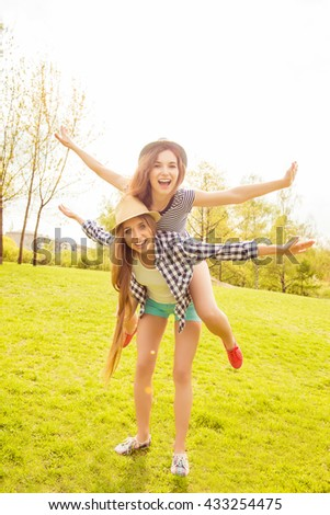 Happy girl piggybacking her friend and gesturing like an airplane - stock photo