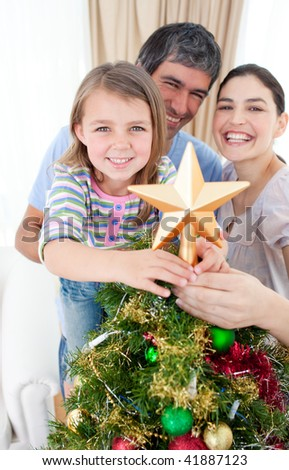 Happy girl placing a Christmas star on the top of a tree - stock photo