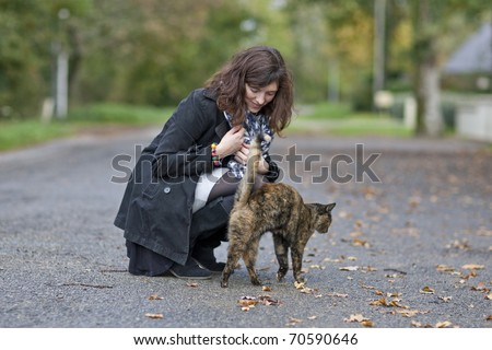 Happy girl playing outdoor with her cat - stock photo